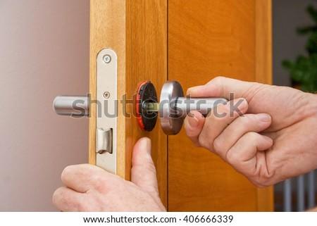 Handyman repairing a door handle - stock photo