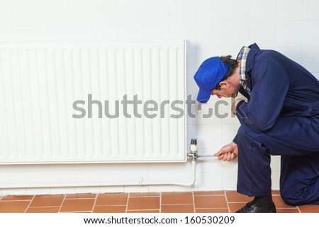 Handyman repairing a radiator in bright room - stock photo