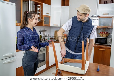Handyman Repairing Furniture In The Kitchen. He Repairs A Chair With A  Screwdriver. The