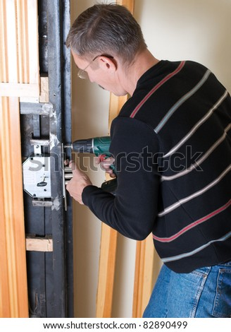 handyman repairing lock with drill - stock photo