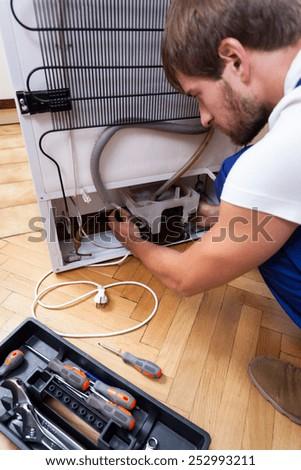 Handyman repairs the broken fridge - stock photo