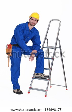 Handyman stood with ladder - stock photo