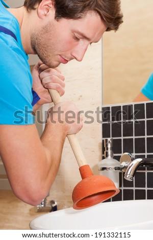 Handyman using plunger for washbasin in bathroom - stock photo