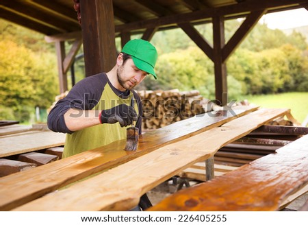 Handyman varnishing pine wooden planks in patio outside the new house - stock photo