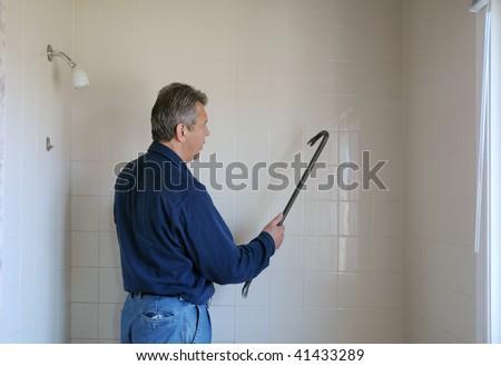 Handyman with a crowbar against bathroom wall - stock photo