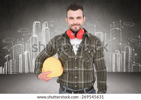 Handyman with earmuffs holding helmet against hand drawn city plan - stock photo