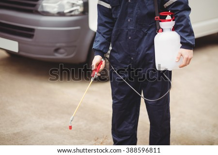Handyman with insecticide standing in front of his van - stock photo