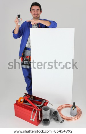 handyman with many tools showing a cell phone - stock photo
