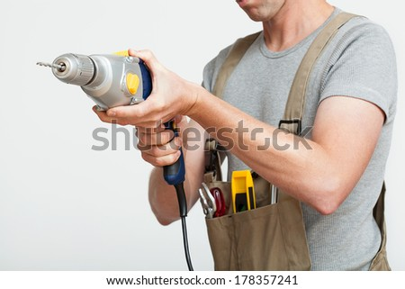 Handyman with silver drill on white isolated background - stock photo