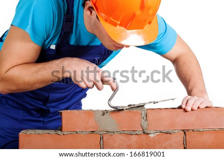 Handyman with trowel installing red brick - stock photo