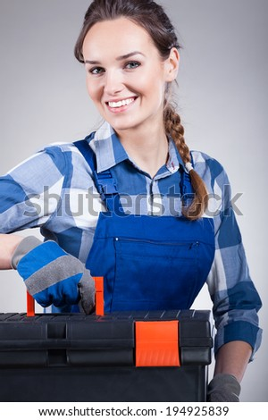 Handywoman with a toolbox ready to work - stock photo