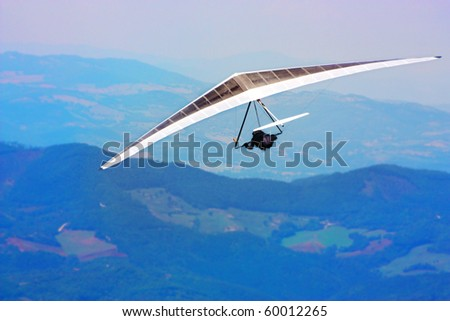 Hang glider flying in the mountains in Italy - stock photo