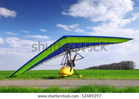 Hang-glider over green grass and blue sky. Ready to fly