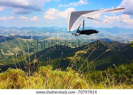 Hang glider pilot in Italian mountains - stock photo