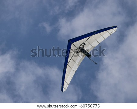 Hang glider soaring against a beautiful cloudscape - stock photo