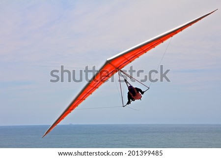 Hang gliding man on an orange wing with sky in the background - stock photo