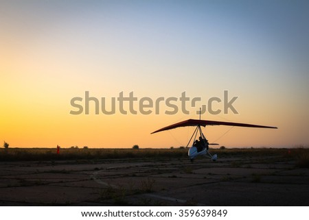 Hang-gliding, standing at dawn on the runway - stock photo