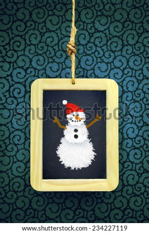 Hanged old slate board with Christmas snowman chalk drawing - stock photo