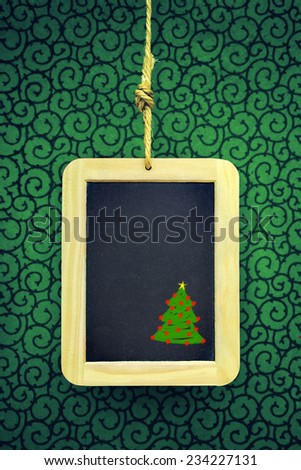 Hanged old slate board with Christmas tree chalk drawing - stock photo