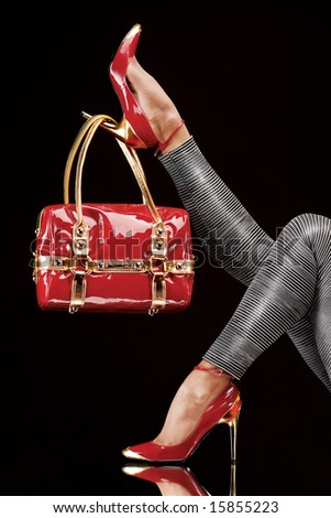 Hanged on heel. Stylish red bag hanging on a chic high-heeled shoe. - stock photo