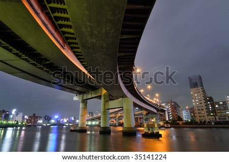hanged up huge highway structure over river waters by night