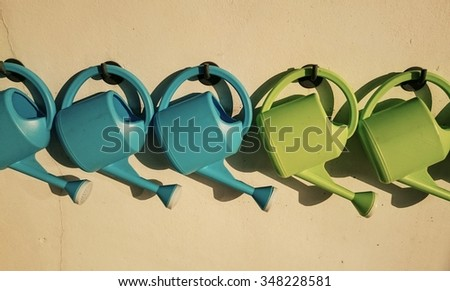 hanged watering pots on the wall - vintage style color - stock photo