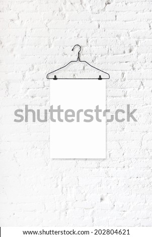 Hanger with white paper on a white brick wall - stock photo