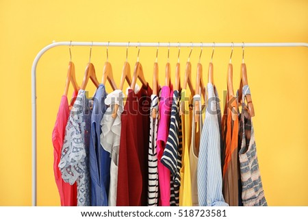 Hangers with different female clothes on yellow background