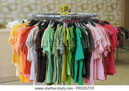 Hangers with t-shirts in store ready to buy - stock photo