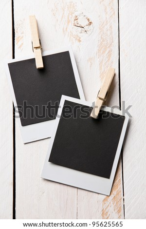 Hanging aged photo frames on wooden background - stock photo