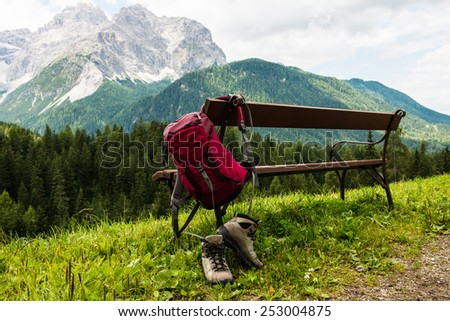 Hanging backpack and hiking shoes with mountains in the background. South Tyrol. - stock photo