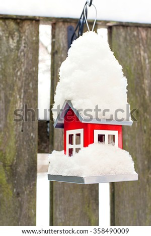 Hanging bird red metal feeder covered by snow in winter. Outdoors vertical closeup image. - stock photo