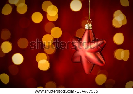 Hanging Christmas Ornament star with sparkling lights in background - stock photo