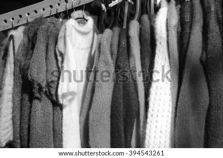 Hanging colorful  knitted colorful clothes - sweaters, dresses, cardigans etc. Aged photo. Black and white. - stock photo