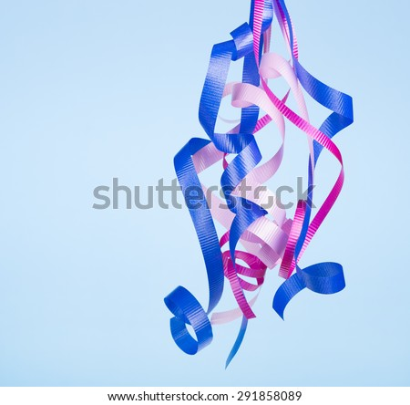 Hanging curled birthday ribbon on a blue background - stock photo
