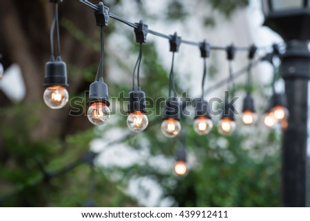 Hanging decorative christmas lights for a wedding party - stock photo