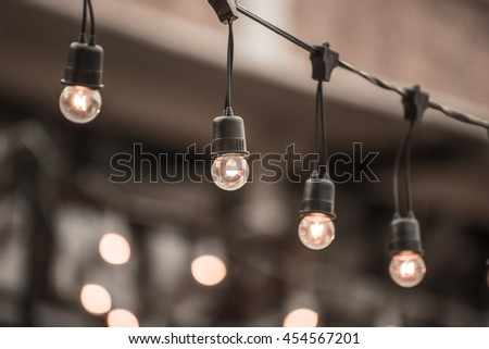 Hanging decorative christmas lights in backyard - stock photo