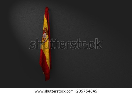 hanging dirty flag of spain in the dark wall - stock photo