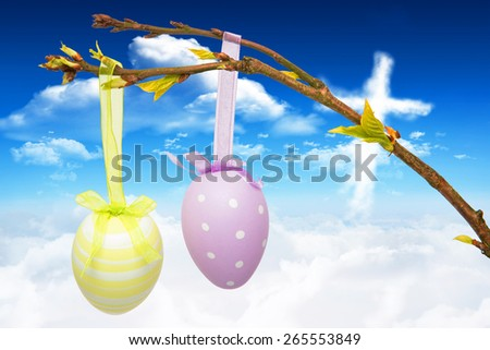 Hanging easter eggs against cross shape in the sky - stock photo