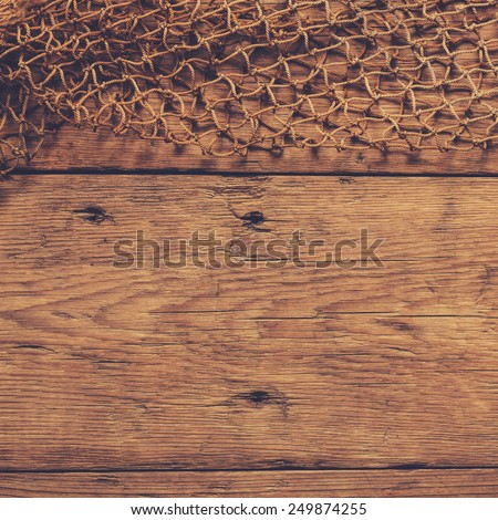 Hanging Fishnet on Wood Wall - stock photo