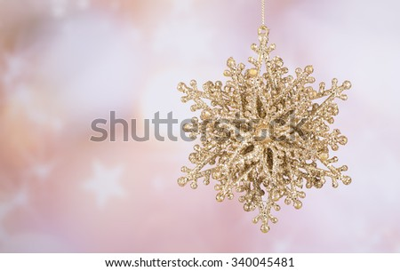 Hanging gold Christmas ornament with a colorful background - stock photo