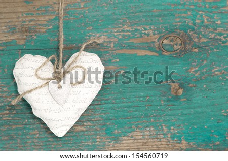 Hanging heart and turquoise wooden background in country style - stock photo