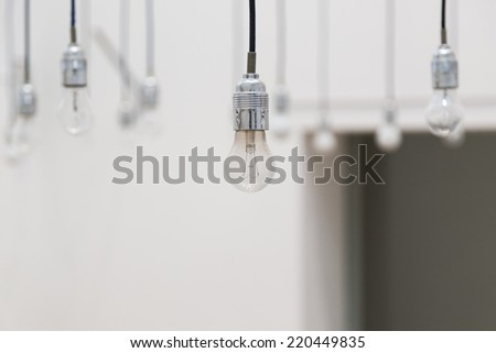 Hanging light bulbs on blurred white background - stock photo