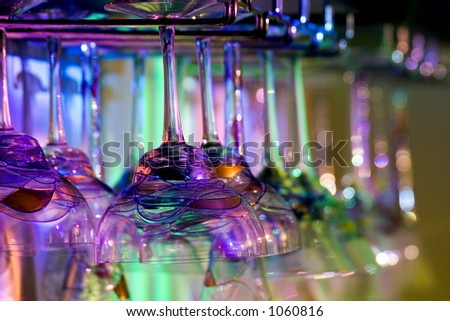 Hanging margarita glasses, martini glasses, red wine glasses and white wine glasses in multi-colored light.