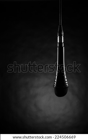 Hanging microphone on black - stock photo
