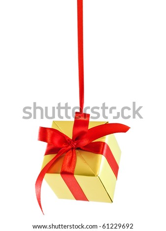 Hanging on a ribbon golden gift wrapped present with red satin bow isolated on white - stock photo