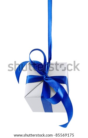 Hanging on a ribbon silver gift wrapped present with blue satin bow isolated on white - stock photo