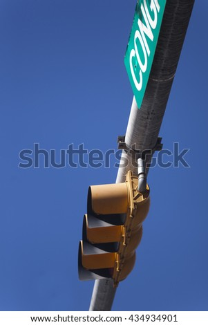 Hanging orange traffic light against a clear blue sky - stock photo