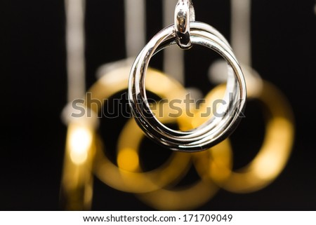hanging platinum rings pendant with gold rings on background