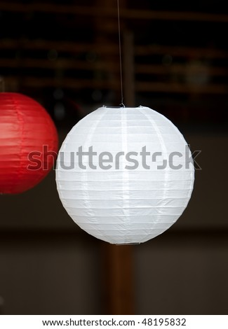 hanging red and white Japanese lantern with dark background - stock photo
